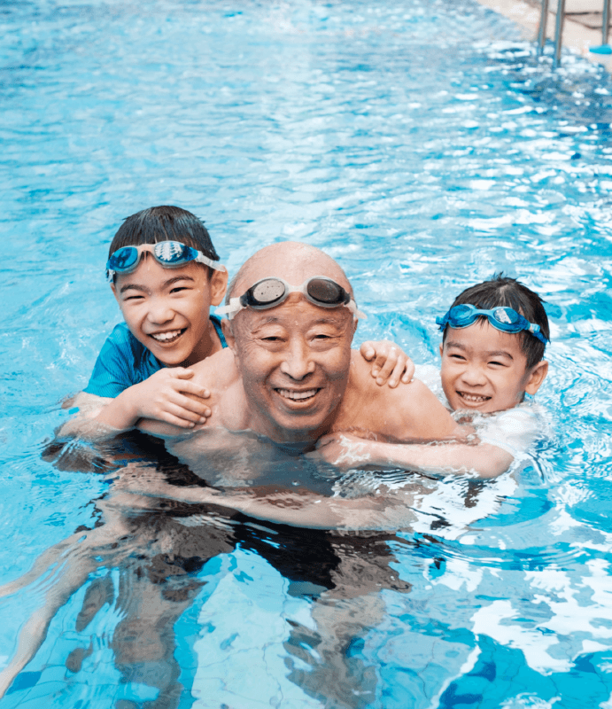 Smiling grandfather and two grandchildren in pool